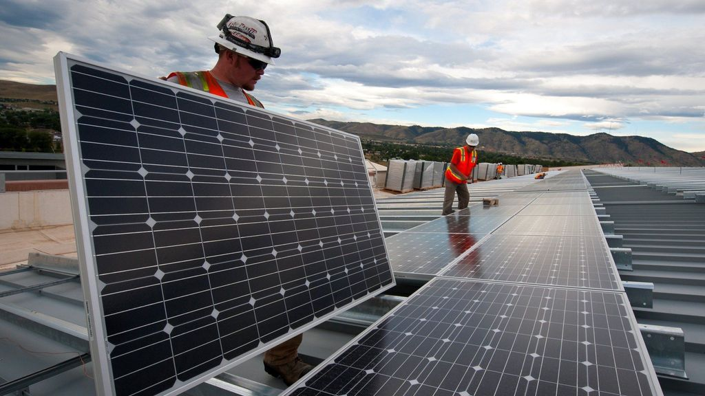 Workers install photovoltaic solar panels on the roof of the National Renewable Energy Laboratory's Research Support Facility in Golden, Colo. in 2013. (Source: U.S. Department of Energy)
